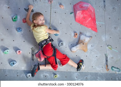 little girl climbing a rock wall indoor