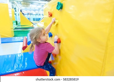Little Girl Climbing a Rock Wall Indoor. Children's Entertainment Sports Soft Ground.
