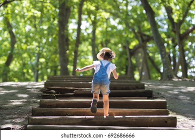 Little girl climbing the stairs in the forest