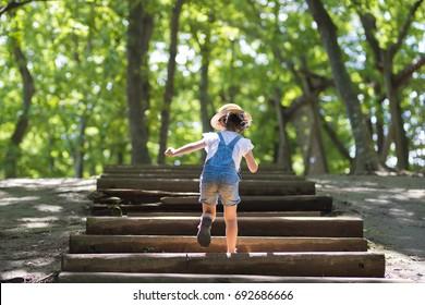 Menina subindo as escadas na floresta