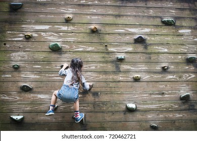 Little girl climbing the wall