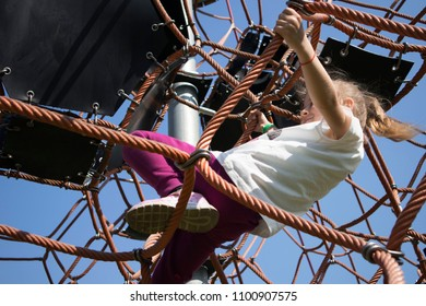 little girl climbs on the grid on the Playground