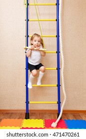 A little girl clings to the bar. Wall bars. Sports Equipment. Children's sports.