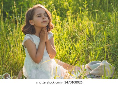 Little Girl closed her eyes, praying in a field during beautiful sunset. Hands folded in prayer concept for faith, spirituality and religion. Peace, hope, dreams concept