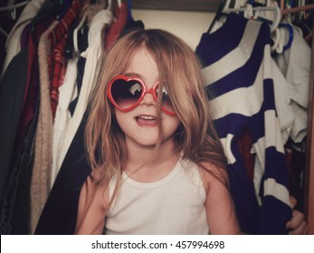 A little girl is in a closet of messy clothes with red glasses for a style or fashion concept.