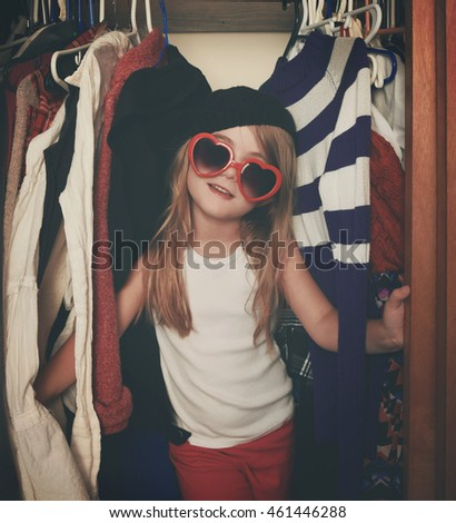 A little girl is in a closet of messy clothes with red glasses for a style, fashion or glamour concept.
