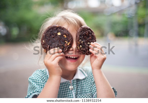 The little girl closing eyes with two big chocolate cookies.