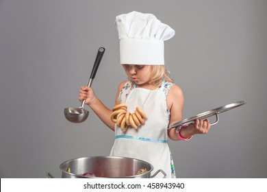 Little girl in the clothes chef hat and apron to cook a delicious meal in a large pot in a studio on a gray background