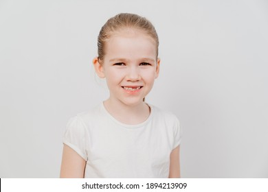 A little girl with collected hair in a white T-shirt stands on a white background and smiles. happy childhood. Children's sport. place for the inscription. a baby tooth fell out