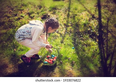 Little girl collects Easter colored eggs during Egg hunt in Spring. Beautiful spring season day.
