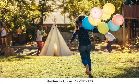 Little girl with colorful balloons running towards kids playing in backyard. Children having fun outdoors.