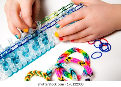 Little girl with colorful nails making a rubber loom bracelet with a hook . Hands close up. Young fashion concept