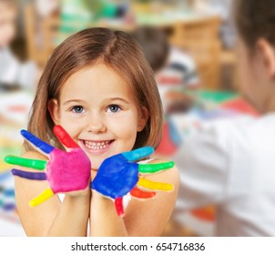 Little girl with colorful painted hands on background.