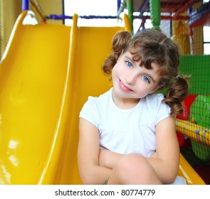 little girl in colorful playground sitting on yellow slide