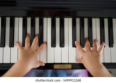 Little girl in colourful dress plays piano
