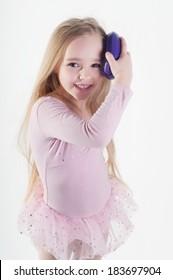 Little girl combing long blond hair in studio