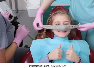 A little girl is comfortable to treat her teeth under superficial sedation. The girl smiles and holds two thumbs up. Milk teeth treatment. Treatment of children's teeth with nitrous oxide.