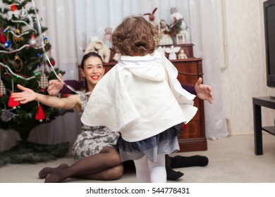 Little girl is coming to mother's opened embrace, view from the back, the mother is sitting under the Christmas tree