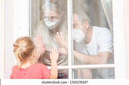 Klein Mädchen kommuniziert mit seinen Großeltern durch ein Fenster während der Epidemie des Coronavirus