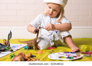 Little girl concentrating whilst painting dinosaur figure .