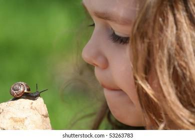 Little girl considers a snail