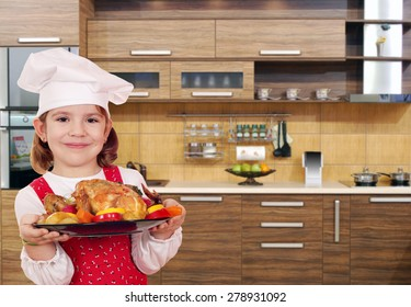 little girl cook with chicken in kitchen
