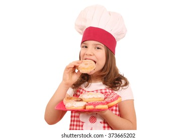 little girl cook eating sweet donuts