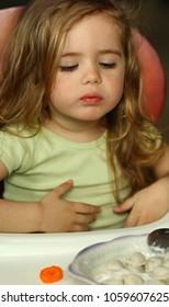 Little girl cooling down dumplings