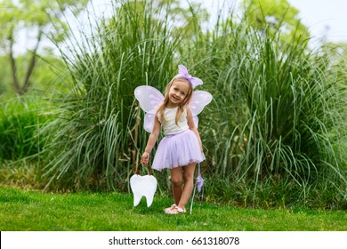 A little girl in the costume of a tooth fairy stands on the street and holds a bag in the shape of a tooth