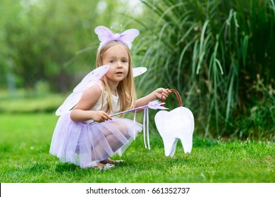 A little girl in the costume of a tooth fairy sitting in the park and holds a bag in the shape of a tooth