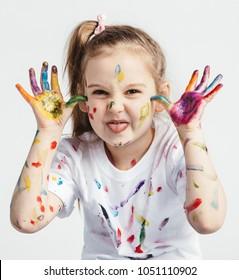 Little girl covered in paint making funny faces. Kindergarten kid. Prankster.