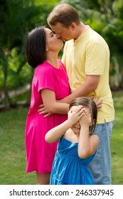Little girl covering her eyes while her parents kissing in the background