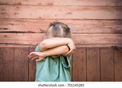 Little girl covering her face with arms