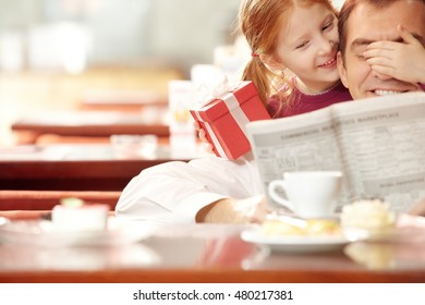 Little girl covering her fathers eyes with one hand and holding gift box in the other