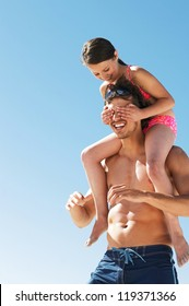 Little girl covers her dads eyes as she is carried on his shoulders while playing at the beach
