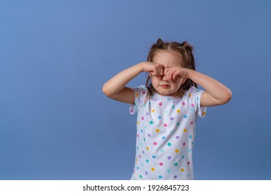 little girl covers her eyes with her hand, on a purple background. The baby is tired, crying and rubbing her eyes with her hands. Copy space.