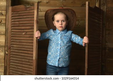 little girl in cowboy hat on wooden background