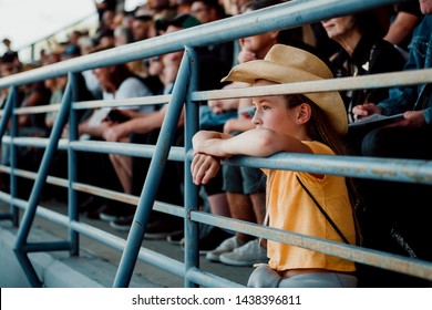 Little girl with a cowboy hat on watching the rodeo