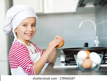 Little girl cracking an egg