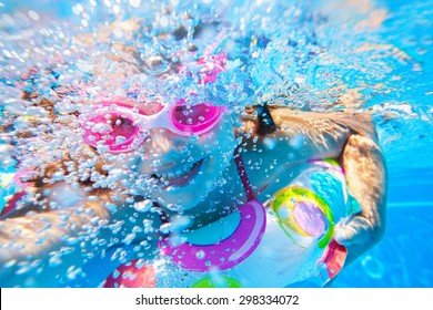 little girl creates bubbles under water in the pool
