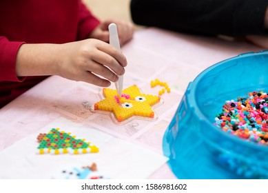 Little girl creates pattern using perler beads. Fusible colorful beads. Toy that develops the imagination and creativity of child. Process close-up