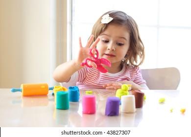 Little girl creating toys from playdough