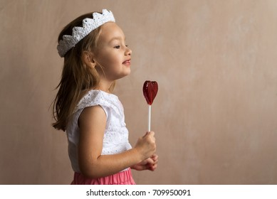 Little girl in a crocheted crown and a pink skirt with a heart-shaped lollipop.