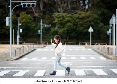 Little girl crossing a pedestrian crossing