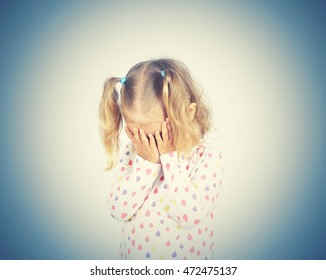 Little girl crying covering his face with his hands.