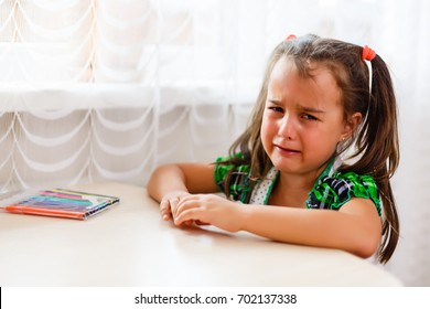Little girl crying doing her homework