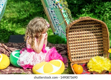 Little girl crying next to a basket of food. Girl naughty at a picnic