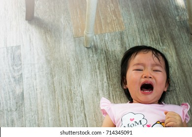 Little girl crying on the floor. Terrible two period.