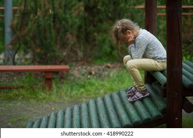 Little girl crying on the playground. Stress, sadness, depression, problems, punishment.