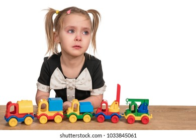 Little girl crying playing toy cars on a trailer, sitting at a wooden table, isolated on a white background